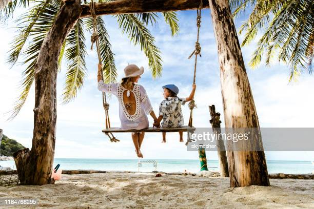 rear view of carefree mother and son holding hands while swinging at the beach. - family vacation stock pictures, royalty-free photos & images