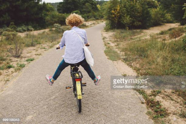 rear view of carefree woman cycling on road - bortes foto e immagini stock