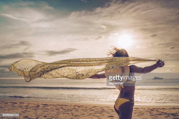 rear view of carefree woman running with a shawl on the beach. - shawl stock pictures, royalty-free photos & images