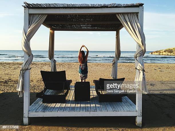 Rear View Of Carefree Woman Standing By Gazebo At Beach