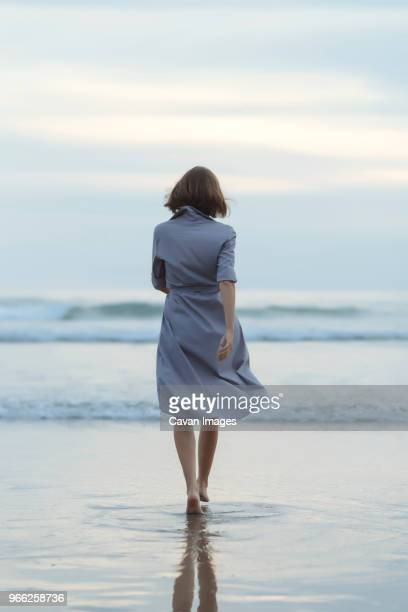 rear view of carefree woman walking towards sea on shore at beach during sunset - donna di spalle al mare foto e immagini stock