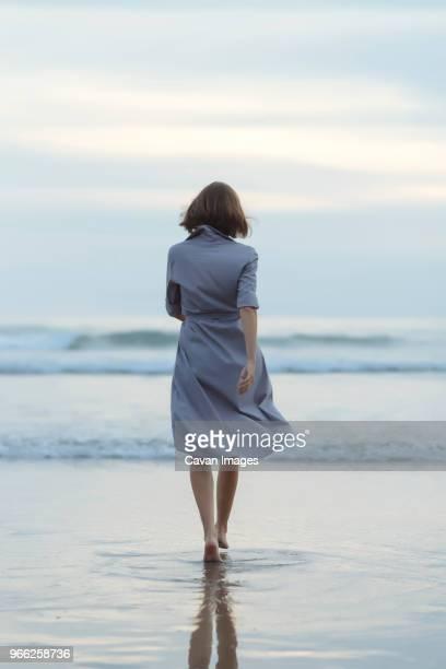 rear view of carefree woman walking towards sea on shore at beach during sunset - frau von hinten stock-fotos und bilder