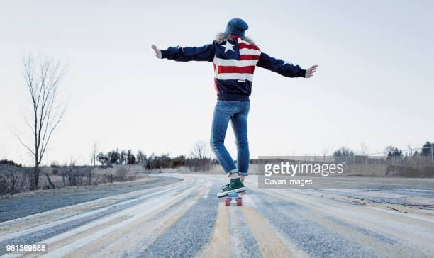 rear view of carefree woman with arms outstretched skateboarding on road against clear sky during winter - les bras écartés photos et images de collection