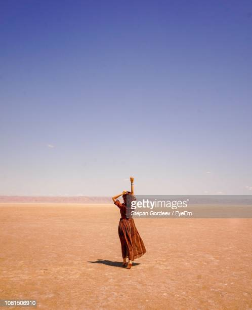 rear view of carefree woman with arms raised walking on desert against sky during sunny day - チュニジア ストックフォトと画像