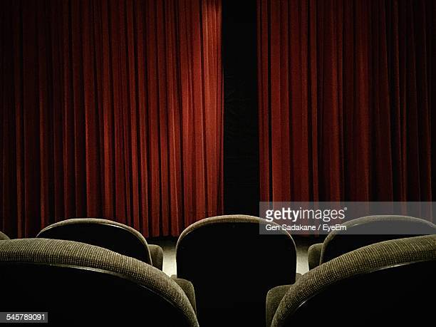 Rear View Of Chairs In Auditorium With Closed Curtains