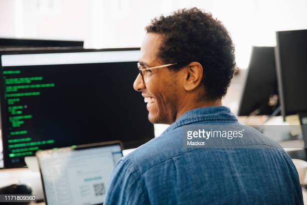 rear view of cheerful male it professional looking away while sitting in creative office - programmer stock pictures, royalty-free photos & images