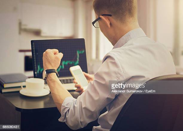 Rear View Of Cheerful Stock Broker With Fist Sitting In Office