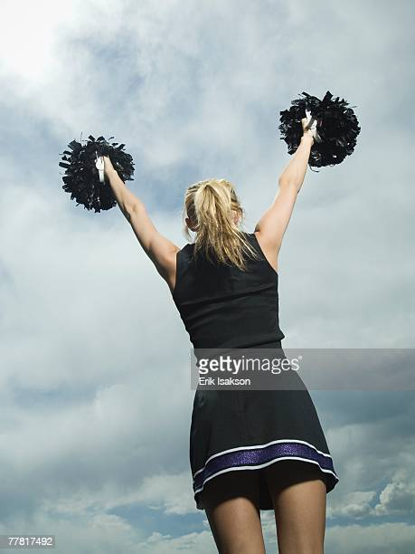 rear view of cheerleader with pom poms - pom pom stock pictures, royalty-free photos & images