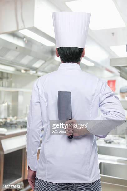 Rear View of Chef with Knife Behind his Back