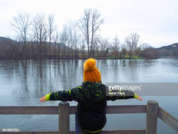 Rear View Of Child On Bridge By Lake During Winter