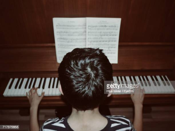 Rear View Of Child Playing Piano