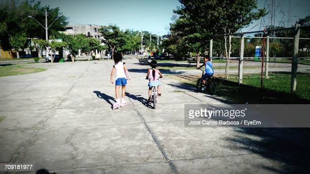 Rear View Of Children On Walkway At Park
