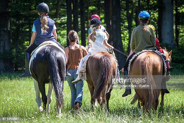 Rear View Of Children Riding Horses On Grassy Field