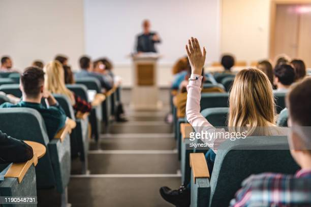 rear view of college student raising her hand in amphitheater. - attending stock pictures, royalty-free photos & images