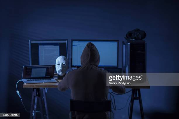 Rear view of computer hacker sitting at desk with equipment against gray background