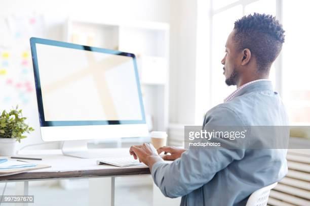 vue arrière du concentré programmeur mâle noir occupé tapant sur le clavier de l'ordinateur tout en travaillant sur le projet de bureau moderne - métier du design photos et images de collection