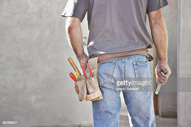 Rear view of construction worker's tool belt