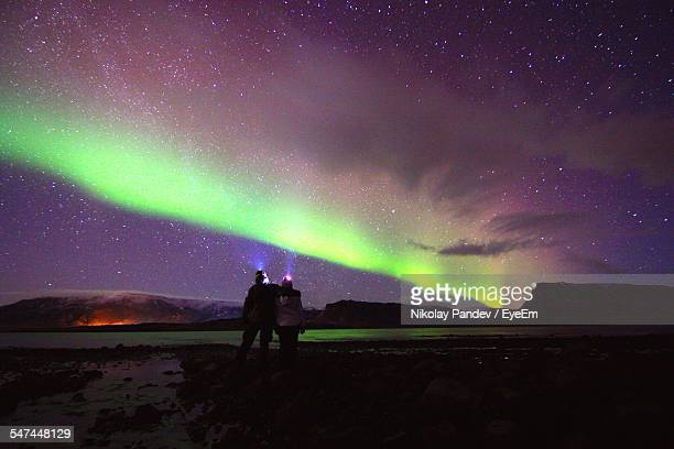 Rear View Of Couple Against Aurora In Sky At Night