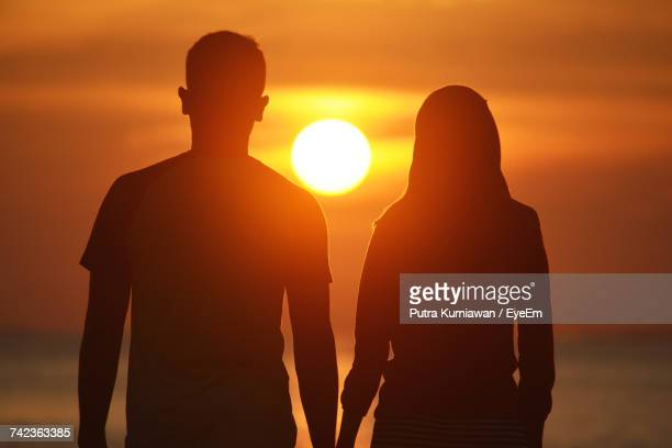 Rear View Of Couple At Beach During Sunset