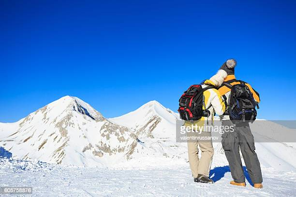 Rear view of couple backpackers hiking in the snow mountain