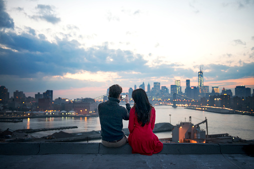 Rear view of couple clicking photograph of illuminated cityscape at dusk - gettyimageskorea