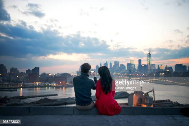 rear view of couple clicking photograph of illuminated cityscape at dusk - indian couples stock pictures, royalty-free photos & images