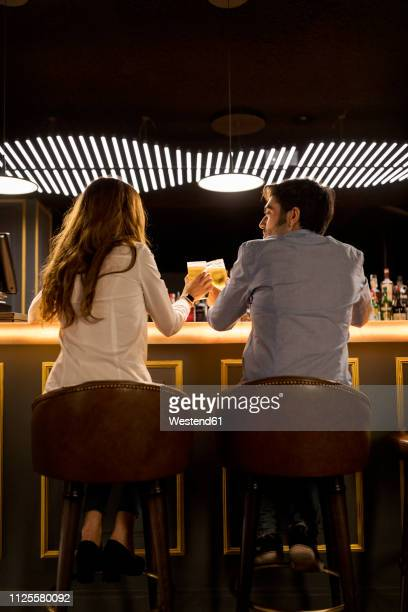 rear view of couple clinking beer glasses in a bar - daten stockfoto's en -beelden