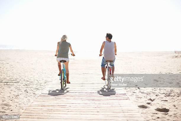 rear view of couple cycling on boardwalk at venice beach, los angeles, california, usa - boardwalk stock pictures, royalty-free photos & images