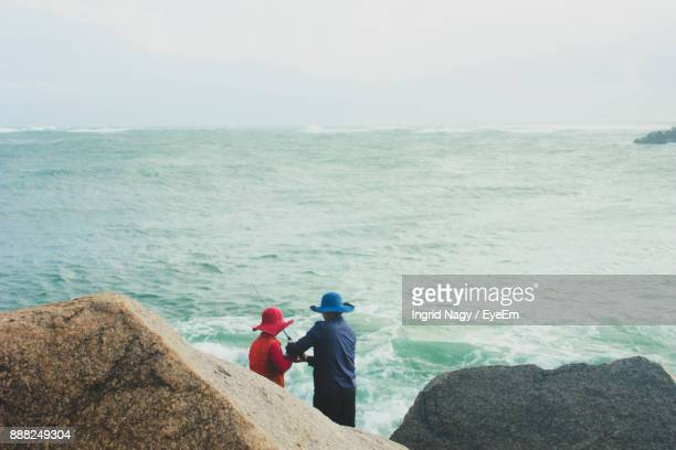 Rear View Of Couple Fishing At Shore Against Sky