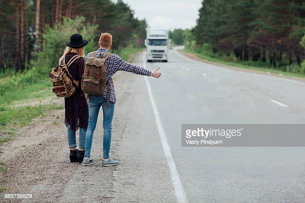 rear view of couple hitchhiking on roadside against trees - hitchhiking stock pictures, royalty-free photos & images