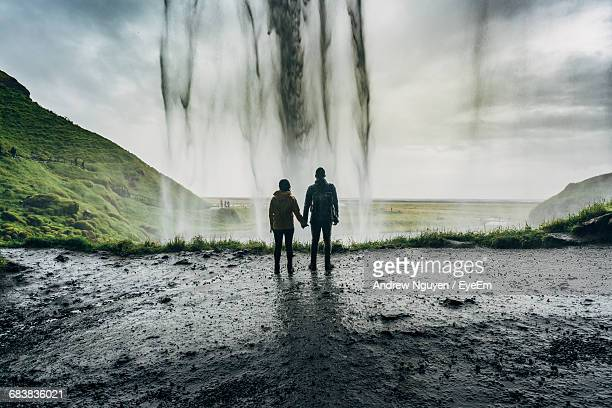 Rear View Of Couple Holding Hands Against Waterfall