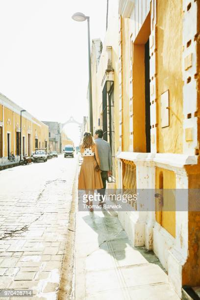 Rear view of couple holding hands and exploring town while on vacation
