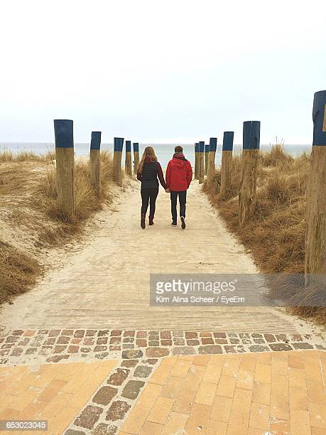 Rear View Of Couple Holding Hands And Walking On Beach