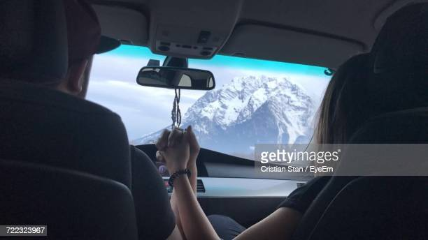 Rear View Of Couple Holding Hands While Driving Car Against Snowcapped Mountain