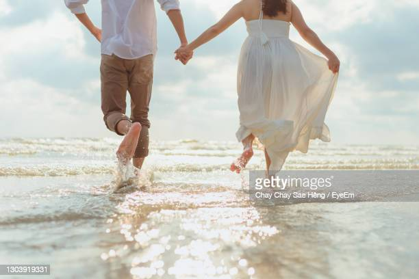 rear view of couple holding hands while running on beach - ceremony stock pictures, royalty-free photos & images