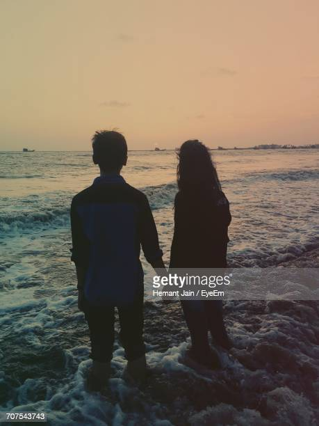 Rear View Of Couple Holding Hands While Standing On Shore During Sunset