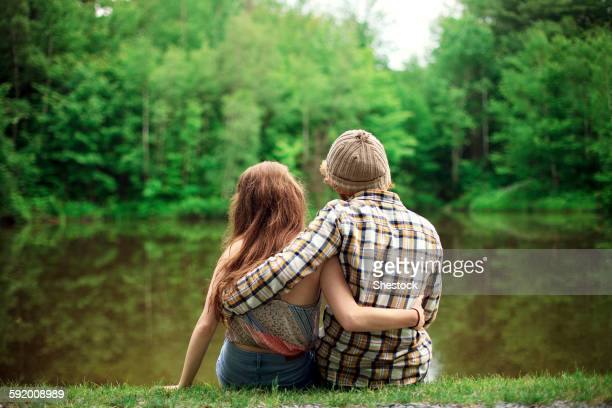 rear view of couple hugging near lake - petite amie photos et images de collection
