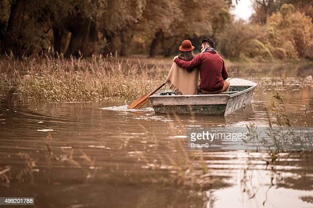 Vista posterior de la pareja en una embarcación durante el otoño día.
