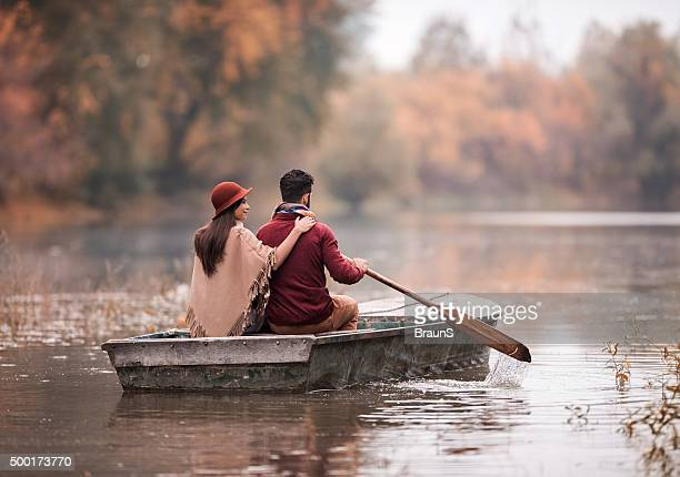Rear view of couple in a boat during autumn day.