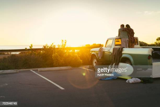 Rear view of couple in back of pickup truck watching sunset at Newport Beach, California, USA