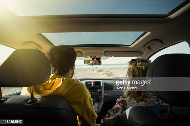 rear view of couple in car at beach on sunny day - road trip stock pictures, royalty-free photos & images
