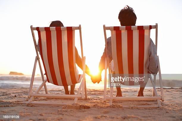 Vista traseira do casal em cadeiras de lugar na praia