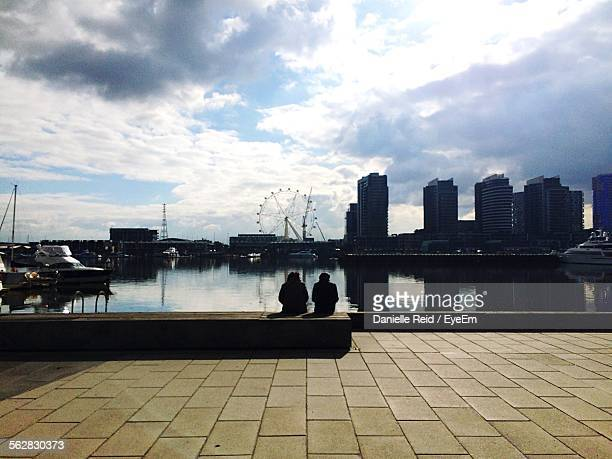 Rear View Of Couple In Front Of River In City Against Cloudy Sky