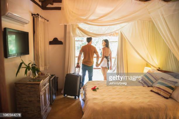 rear view of couple in hotel room holding hands - honeymoon stock pictures, royalty-free photos & images