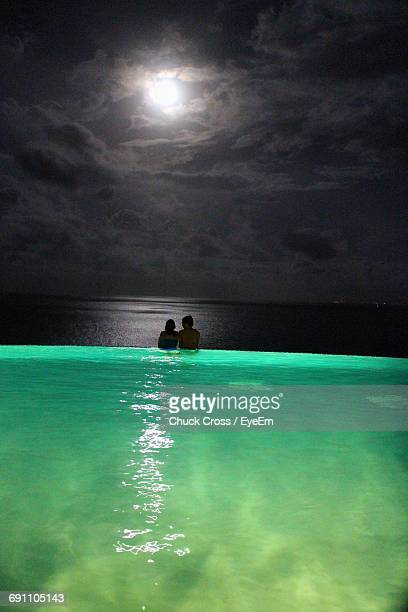 rear view of couple in infinity pool against sea at las casitas village a waldorf astoria resort - moonlight lovers stock-fotos und bilder