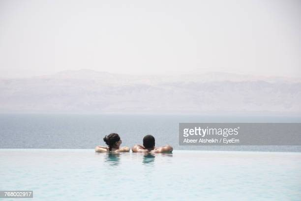 rear view of couple in infinity pool against sea - infinity pool stock pictures, royalty-free photos & images