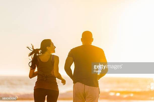 Rear view of couple jogging at beach during sunset