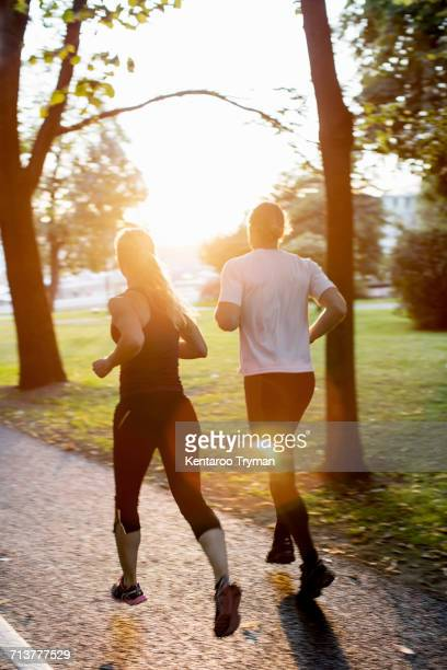 Rear view of couple jogging on footpath at park during sunrise