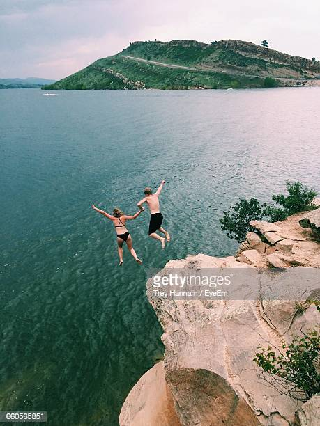 Rear View Of Couple Jumping From Cliff In Sea
