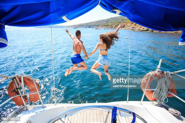 Rear view of couple jumping into ater